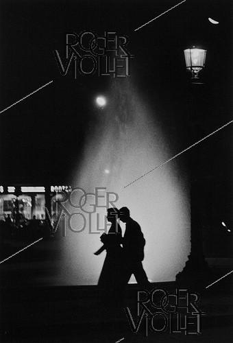 Roger-Viollet | 294224 | Couple in front of the lit-up fountains of the Champs-Élysées roundabout by night. Paris (VIIIth arrondissment), 1957. Photograph by Janine Niepce (1921-2007). | © Janine Niepce / Roger-Viollet