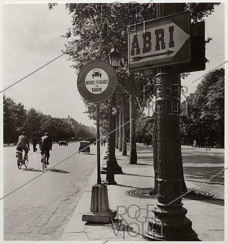 Roger-Viollet | 882376 | Cyclists, road signs indicating a shelter and banning French tourist cars, boulevard des Champs-Elysées, Paris (VIIIth arrondissement). 1942. Photograph by Roger Schall (1904-1995). Paris, musée Carnavalet. | © Roger Schall / Musée Carnavalet / Roger-Viollet