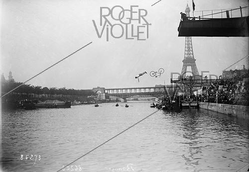 Roger-Viollet | 753130 | Delbord diving on a bicycle during the French diving championship. Paris, on June 22, 1913. | © Maurice-Louis Branger / Roger-Viollet