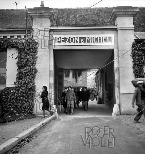 Roger-Viollet | 582300 | Employees leaving the Etablissements Pezon et Michel, manufacture for fishing rods. Amboise (Indre-et-Loire), circa 1945. | © Tony Burnand / Roger-Viollet