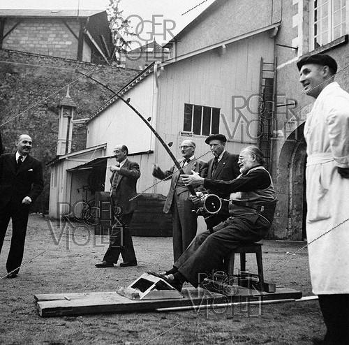 Roger-Viollet | 444741 | Ernest Hemingway (1899-1961), American writer, Pierre Creusevant, casting champion (wearing a beret) and André Pezon, testing a fishing rod for deep-sea fishing, during a trip of the writer in France. Amboise (Pezon company). | © Tony Burnand / Roger-Viollet