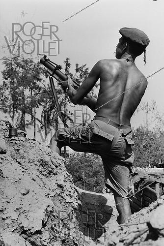 Roger-Viollet | 246732 | Fighter of the People's Movement for the Liberation of Angola attacking the Portuguese troops with a grenade launcher. Angola (Black Africa), 1975. | © Françoise Demulder / Roger-Viollet