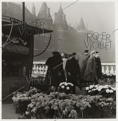 Roger-Viollet | 943645 | Flower market at All Saints, view on the Conciergerie from the quai de Gesvres and the pont-au-Change, Paris (Ist arrondissement). 1941. Photograph by Roger Schall (1904-1995). Paris, musée Carnavalet. | © Roger Schall / Musée Carnavalet / Roger-Viollet