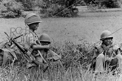 Roger-Viollet | 637074 | Front-line on the road number 5. Soldiers among whom a teenager, equipped with a M16 from the US Army, having a break. Cambodia, 1974. | © Françoise Demulder / Roger-Viollet
