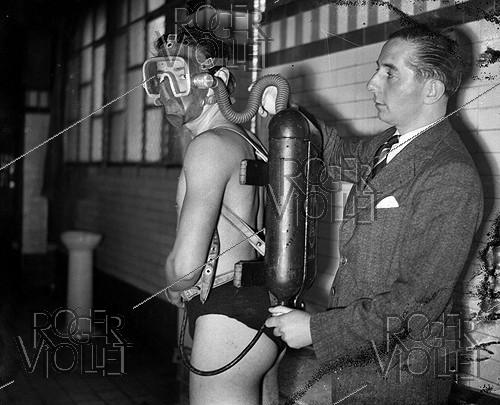 Roger-Viollet | 485012 | Georges Commeines, French inventor, putting on a experimenter his appliance to dive at 55 meters. Paris, Ledru-Rollin swimming-pool, February 1944. | © LAPI / Roger-Viollet