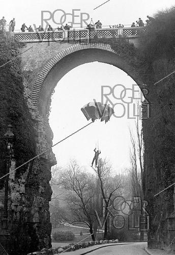 Roger-Viollet | 627571 | Germaine Granveaud parachuting down the Pont des Suicidés (27 meters) at the Buttes-Chaumont. Paris. | © Roger-Viollet / Roger-Viollet