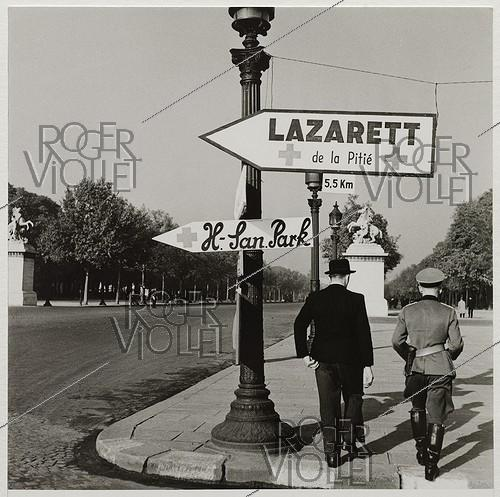 Roger-Viollet | 227376 | German officer and civilian at the end of the avenue des Champs-Elysées, near signs indicating  Lazarett de la pitié  and  H-Lan.Park , place de la Concorde, Paris (Ist-VIIIth arrondissements). 1942. Photograph by Roger Schall (1904-1995). Paris, musée Carnavalet. | © Roger Schall / Musée Carnavalet / Roger-Viollet