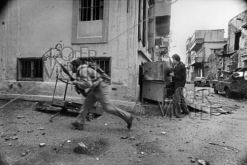 Roger-Viollet | 227207 | Lebanese civil war. Christian militiamen, members of the Kataeb party, running after Palestinian from the Quarantine district. Beirut (Lebanon), January 1976. | © Françoise Demulder / Roger-Viollet