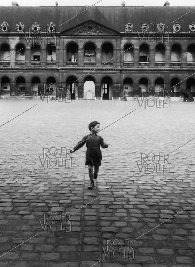 Roger-Viollet | 372294 | Little boy in the courtyard of the Invalides. Paris (VIIth arrondissement), 1953. Photograph by Janine Niepce (1921-2007). | © Janine Niepce / Roger-Viollet