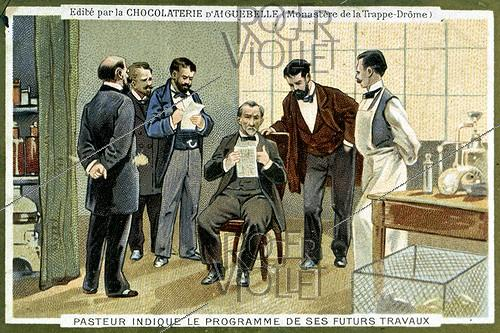 Roger-Viollet | 569035 | Louis Pasteur (1822-1895), French biologist, indicates the programme of his future works. Advertising illustration for the chocolate of Aiguebelle. | © Roger-Viollet / Roger-Viollet