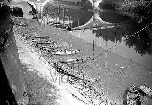 Roger-Viollet | 1016857 | Lowering of the Seine water level in Paris. Small boats grounded in the mud. August, 1942. | © LAPI / Roger-Viollet