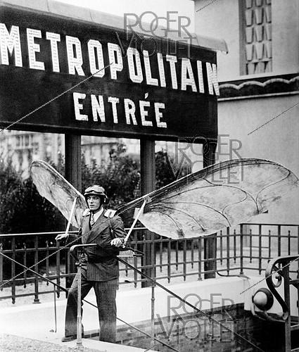 Roger-Viollet | 1039371 | Man with hang gliders. Concours Lépine, French invention competition. Paris, 1935. | © Jacques Boyer / Roger-Viollet
