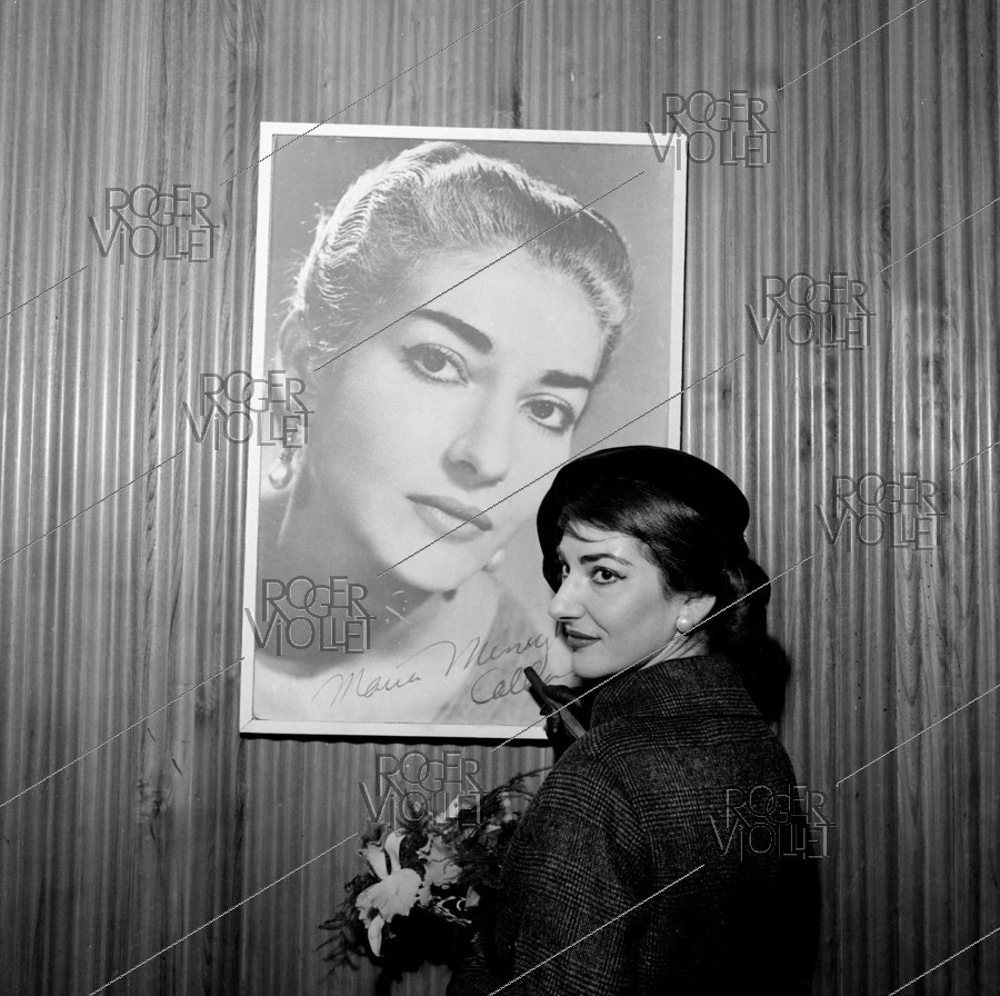 Roger-Viollet | 648449 | Maria Callas (1923-1977), Greek opera singer, signing her photograph. Paris, on January 16, 1958. | © Claude Poirier / Roger-Viollet