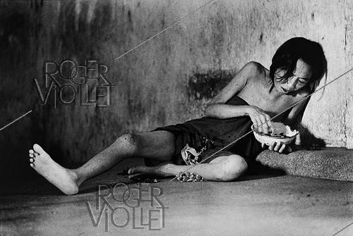 Roger-Viollet | 309996 |  Meal at the asylum . Patient confined in a mental hospital. Saigon (Vietnam), 1975. | © Françoise Demulder / Roger-Viollet