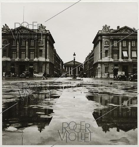 Roger-Viollet | 587188 | Mounted police, view on the palaces by Ange-Jacques Gabriel (Hôtel Crillon) and the Madeleine church, at the place de la Concorde. Paris (Ist and VIIIth arrondissements), 1937. Photograph by Roger Schall (1904-1995). Paris, musée Carnavalet. | © Roger Schall / Musée Carnavalet / Roger-Viollet