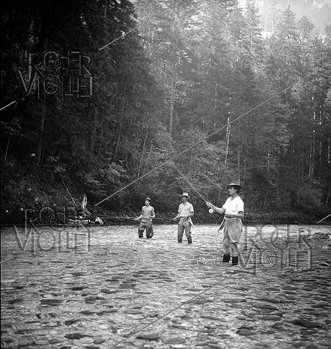 Roger-Viollet | 659792 | Mrs Edouard Vernhes, woman(wife) of the banker, and Tony Burnand angling in torrent. | © Tony Burnand / Roger-Viollet