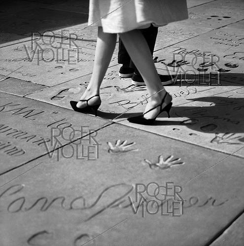 Roger-Viollet | 949770 | Names and prints of famous movie stars in front of the Grauman's Chinese Theater. Hollywood (Los Angeles, California, United States), March 1964. Photograph by Hélène Roger-Viollet (1901-1985) and Jean Fischer (1904-1985). | © Hélène Roger-Viollet & Jean Fischer / Roger-Viollet