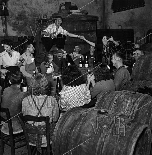 Roger-Viollet | 309588 | On the last day of grape harvest, they celebrate the  paulée , feasting around the table. France, 1950. Photograph by Janine Niepce (1921-2007). | © Janine Niepce / Roger-Viollet