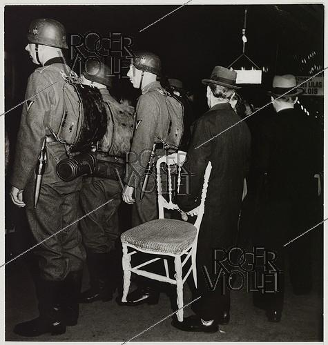 Roger-Viollet | 558555 | On the underground platform, German soldiers and a man carrying a chair, underground station, direction  porte des Lilas . Paris (VIIIth arrondissement), 1943. Photograph by Roger Schall (1904-1995). Paris, musée Carnavalet. | © Roger Schall / Musée Carnavalet / Roger-Viollet