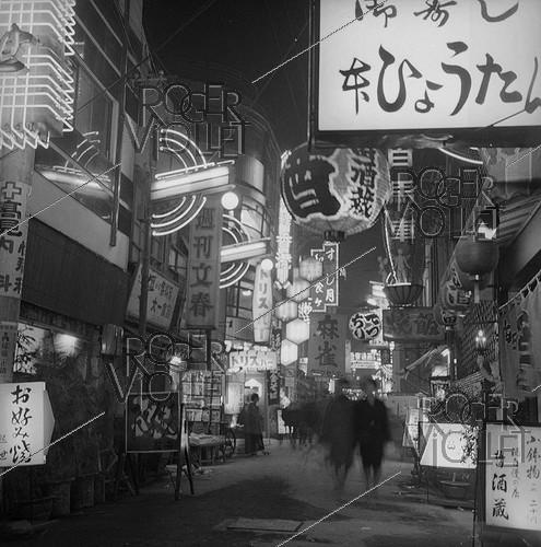 Roger-Viollet | 967827 | Osaka (Japan). A street in the entertainment district, near the central train station. by night. March 1962. | © Roger-Viollet / Roger-Viollet