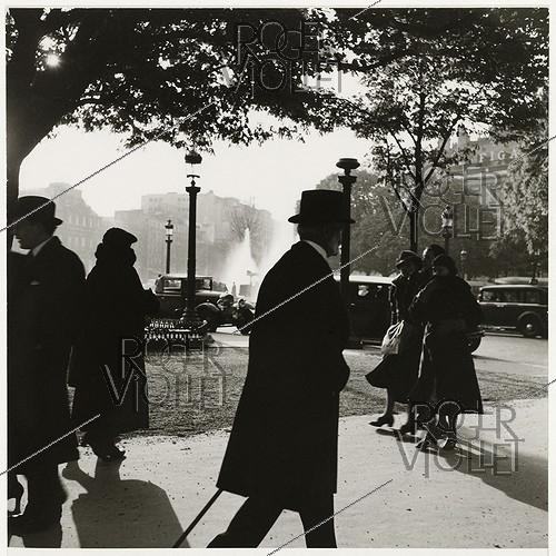 Roger-Viollet | 863974 | Passers-by at the roundabout of the Champs-Elysées. Paris (VIIIth arrondissement), 1937. Photograph by Roger Schall (1904-1995). Paris, musée Carnavalet. | © Roger Schall / Musée Carnavalet / Roger-Viollet