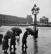 Roger-Viollet | 706915 | Passers-by in front of the triumphal arch of the Carrousel and the Louvre museum. Paris (Ist arrondissement), 1955. Photograph by Janine Niepce (1921-2007). | © Janine Niepce / Roger-Viollet