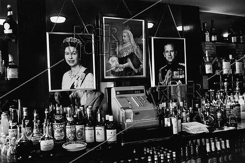 Roger-Viollet | 668284 | Portraits of the queen Elizabeth II, the Queen Victoria, the Prince Philipp of Edinburg in a pub. Brighton (England), on August 5, 1980. | © Jean-Pierre Couderc / Roger-Viollet