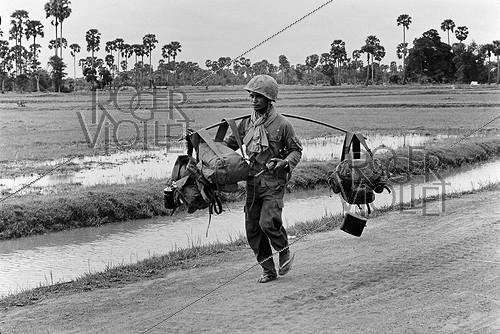 Roger-Viollet | 444241 | Soldier in charge of supplies in the ricefields near the front. Cambodia, 1974. | © Françoise Demulder / Roger-Viollet