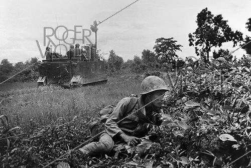 Roger-Viollet | 333066 | Soldier under the cover of a M113 tank. Cambodia, 1974. | © Françoise Demulder / Roger-Viollet