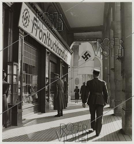 Roger-Viollet | 564548 | The arcade on the rue de Rivoli, the bookshop Smith now  Frontbuchhandlung , nazi flags, rue de Rivoli, Paris (Ist arrondissement). 1942. Photograph by Roger Schall (1904-1995). Paris, musée Carnavalet. | © Roger Schall / Musée Carnavalet / Roger-Viollet