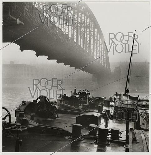 Roger-Viollet | 786259 | The metro bridge and the barges, quai d'Ivry, Paris (XII-XIIIth arrondissements). 1937. Photograph by Roger Schall (1904-1995). Paris, musée Carnavalet. | © Roger Schall / Musée Carnavalet / Roger-Viollet