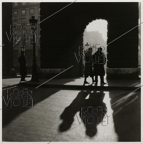 Roger-Viollet | 978353 | Three men in front of the porte Saint-Denis, boulevard Saint-Denis, Paris (Xth arrondissement). 1936. Photograph by Roger Schall (1904-1995). Paris, musée Carnavalet. | © Roger Schall / Musée Carnavalet / Roger-Viollet