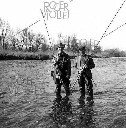 Roger-Viollet | 1027814 | Tony Burnand (on the left) and Chaussabel while salmon fishing. | © Roger-Viollet / Roger-Viollet