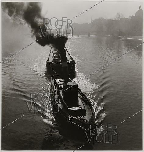 Roger-Viollet | 415994 | Tugboat on the Seine river, barges, view on the dome of the French Institute and the pont des Arts, Paris (VIIth arrondissement). 1936. Photograph by Roger Schall (1904-1995). Paris, musée Carnavalet. | © Roger Schall / Musée Carnavalet / Roger-Viollet