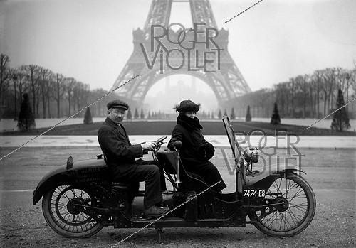 Roger-Viollet | 613806 | Two-seater motorcycle at the Champ-de-Mars. Paris, 1922. | © Jacques Boyer / Roger-Viollet