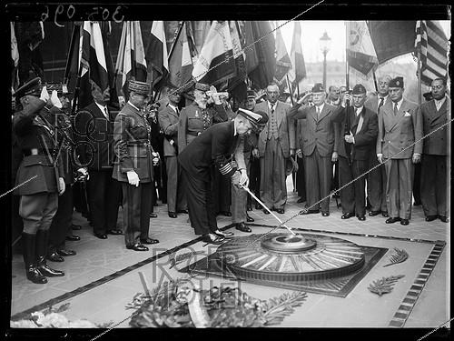 Roger-Viollet | 408631 | U.S. officer rekindling the Flame at the Tomb of the Unknown Soldier for Independence Day. Ceremony in the presence of Henri Gouraud (1867-1946), French General, and William C. Bullitt (1891-1967), American ambassador to France. Paris (VIIIth arrondissement), on July 4, 1939. Photograph from the collections of the newspaper  Excelsior . | © Excelsior - L'Equipe / Roger-Viollet