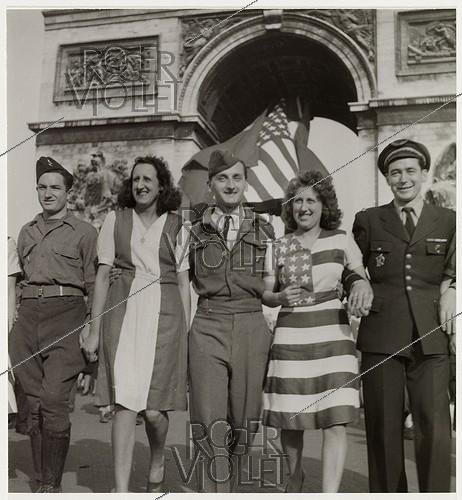Roger-Viollet | 157224 | US soldiers and French women wearing dresses with the colours of the French and American flags, in front of the Arc de Triomphe, present place Charles-de-Gaulle-Etoile. Paris (VIIIth, XVIth, XVIIth arrondissement), 1945. Photograph by Roger Schall (1904-1995). Paris, musée Carnavalet. | © Roger Schall / Musée Carnavalet / Roger-Viollet