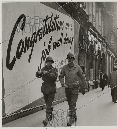 Roger-Viollet | 811699 | US soldiers in front of a poster  Congratulations on a job well done , rue de la Paix. Paris (IInd arrondissement), 1945. Photograph by Roger Schall (1904-1995). Paris, musée Carnavalet. | © Roger Schall / Musée Carnavalet / Roger-Viollet