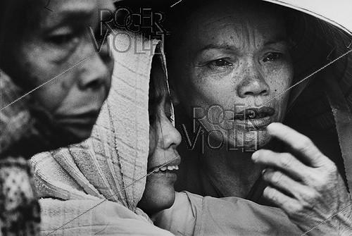 Roger-Viollet | 215945 | Vietnam War (1955-1975). Family in tears during a funeral at the military cemetery of Bien Hoa, 1975. | © Françoise Demulder / Roger-Viollet