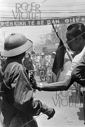 Roger-Viollet | 661616 | Vietnam War (1955-1975). Inhabitant congratulating a soldier a few hours after the fall of Saigon (Vietnam), 1975. | © Françoise Demulder / Roger-Viollet