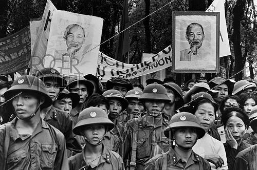Roger-Viollet | 331527 | Vietnam War (1955-1975). Fall of Saigon. Under the portrait of  Uncle Ho , North Vietnamese soldiers in Saigon (Vietnam), 1975. | © Françoise Demulder / Roger-Viollet