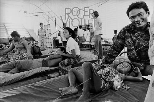 Roger-Viollet | 985470 | Vietnam War. Wounded child at the hospital with his father, he died a few days later. Saigon, 1975. The original caption said: 1/4, the death of a child.  The father seems happy to see his wounded son settled on a bed at the hospital . | © Françoise Demulder / Roger-Viollet