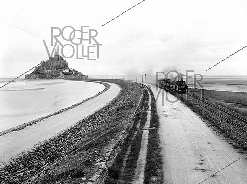 Roger-Viollet | 355107 | View towards the South. The train departure on the dike. Mont-Saint-Michel (France). | © Neurdein / Roger-Viollet