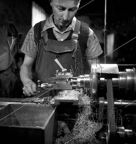 Roger-Viollet | 712622 | Worker making metal ferrules at the Etablissements Pezon et Michel, manufacture for fishing rods. Amboise (Indre-et-Loire), circa 1945. | © Tony Burnand / Roger-Viollet