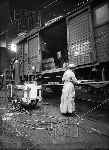 Roger-Viollet | 513790 | World War I. Railway car maintenance in France. Woman using a welding machine. France, 1918. | © Jacques Boyer / Roger-Viollet