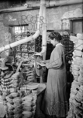 Roger-Viollet | 325816 | World War I. Woman working at producing trench clogs. Soles pumiced by grindstone. | © Jacques Boyer / Roger-Viollet