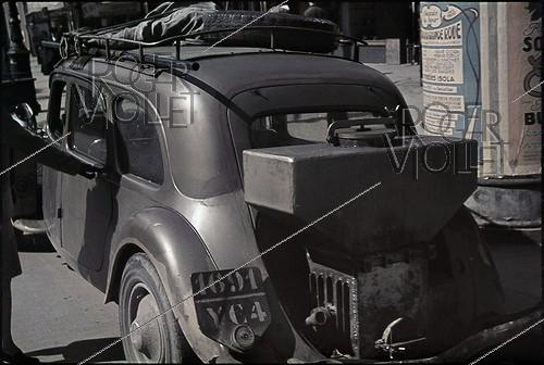 Roger-Viollet | 776632 | World War II. Car equipped with a gas generator, working with charcoal. Paris, April 1942. Photograph by André Zucca (1897-1973). Bibliothèque historique de la Ville de Paris. | © André Zucca / BHVP / Roger-Viollet
