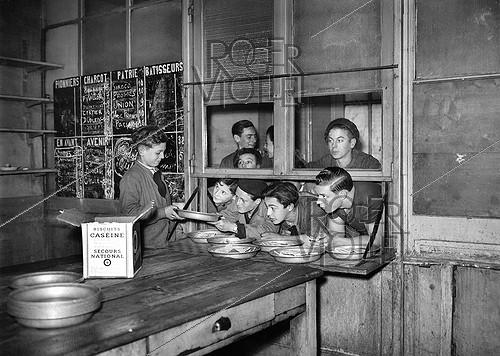Roger-Viollet | 1040400 | World War II. Casein biscuit distribution in a Youth Centre. Paris, December 1941. | © LAPI / Roger-Viollet
