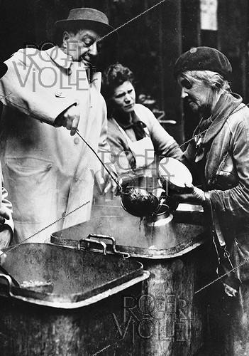 Roger-Viollet | 930295 | World War II. French actor Raimu (1883-1946), serving hot broth to poor people. Paris, the Halles, April 1944. | © LAPI / Roger-Viollet