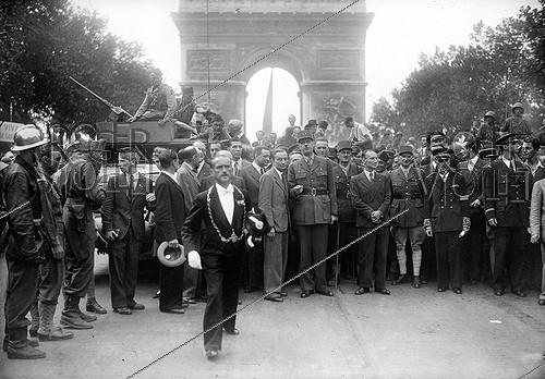 Roger-Viollet | 457563 | World War II. General Charles de Gaulle, at the Arc de Triomphe, with Joseph Laniel, Georges Bidault, General Leclerc, Alexandre Parodi, General Juin, Marcel Flouret, prefect of the Seine and Geoffroy de Courcel (second row, second from the left, profile). On the left : Pierre Dessance (St Cyr forage cap) in the police contingent of the parade. Paris, on August 26, 1944. | © LAPI / Roger-Viollet